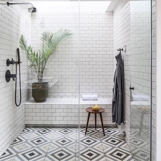 a monochromatic shower space with white subway tiles and a tiled built-in bench plus mosaic floors