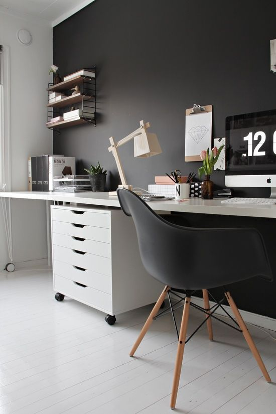 a moody Scandi home office with a black statement wall, chair and soem decor and white as the base