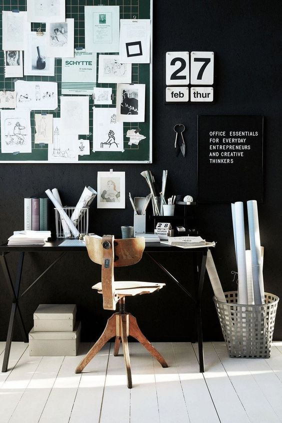 a moody black home office with white floors, a green noteboard with nots, black and white signs and a desk