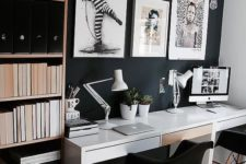 a moody contemporary home office with a black statement wall, a white desk, artworks and a shelving unit