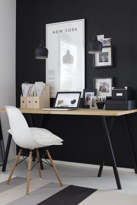 a moody home office with a black statement wall, pendant lamps, a desk with black legs and black framed artworks