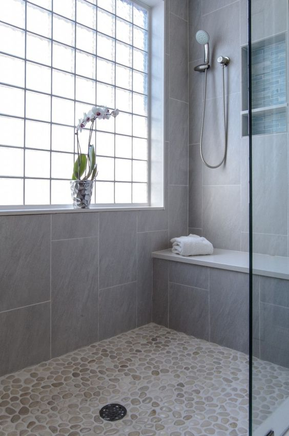 a neutral shower space with a pebble floor and grey tiles, a window with framing and a built-in bench