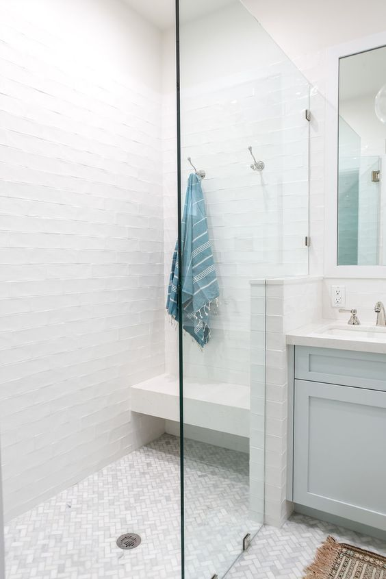 a pure white shower space with a floating bench and a marble tile floor plus seamless glass doors looks ethereal