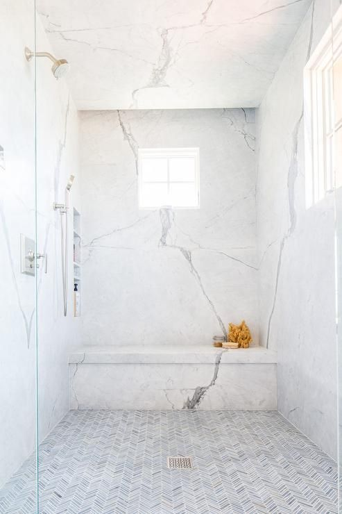 a refiend shower with thin gray marble herringbone floor tiles, marble slab walls featuring stacked shower niches and a marble shower bench