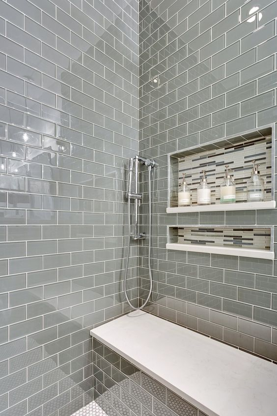 a shiny grey tile shower space with a built-in bench with a white seat and some catchy niches in the wall