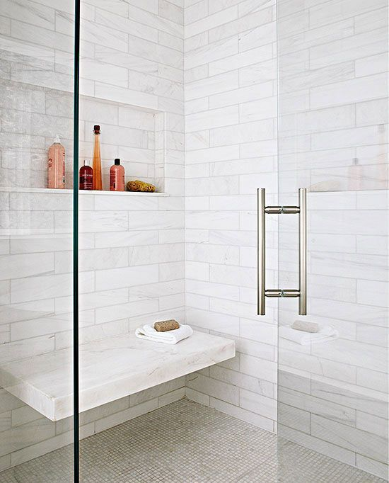 a shower space done with white marble tiles, smaller ones on the floor and a marble floating bench