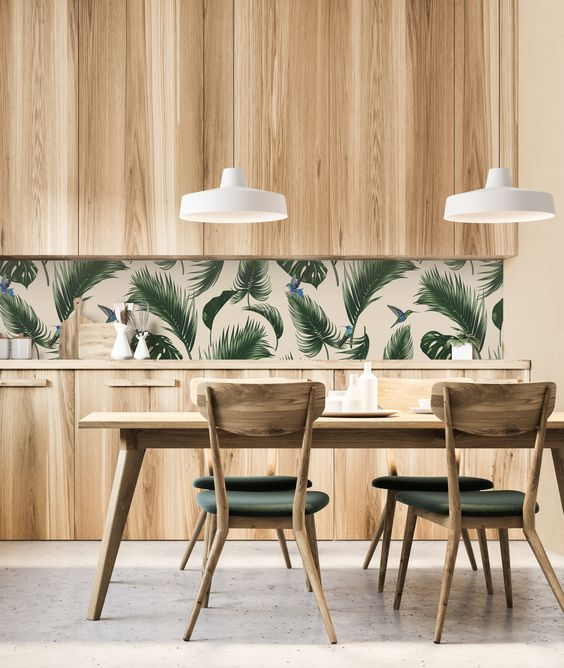 a simple and laconic tropical kitchen with plywood cabinets, a tropical leaf backsplash, a wooden table and upholstered chairs