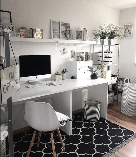 a simple black and white home office with a printed rug, white furniture, a metal shelving unit
