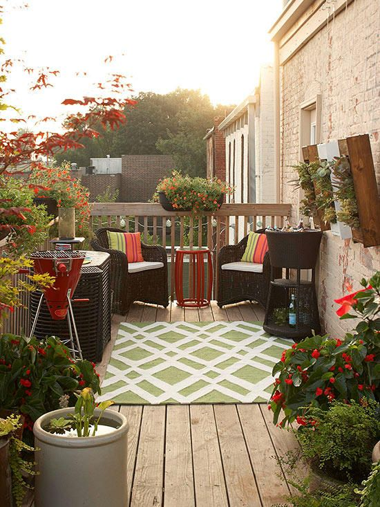 a small and bright deck with simpel woven furniture, colorful upholstery, a grill and potted greenery and flowers
