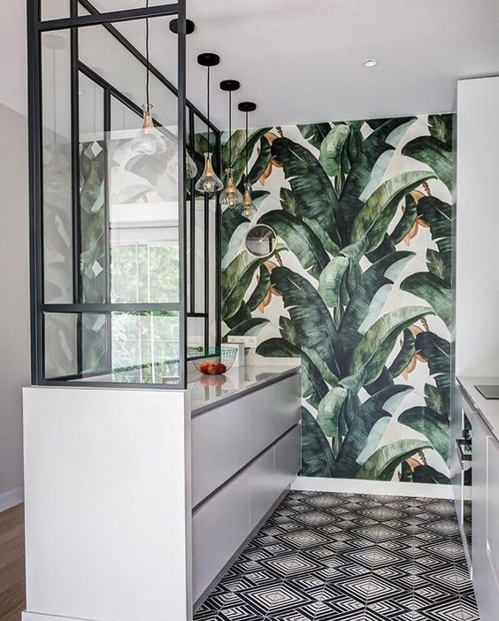 a small and minimalist tropical kitchen with sleek white cabinets, a mosaic floor and a torpical leaf statement wall and pendant lamps