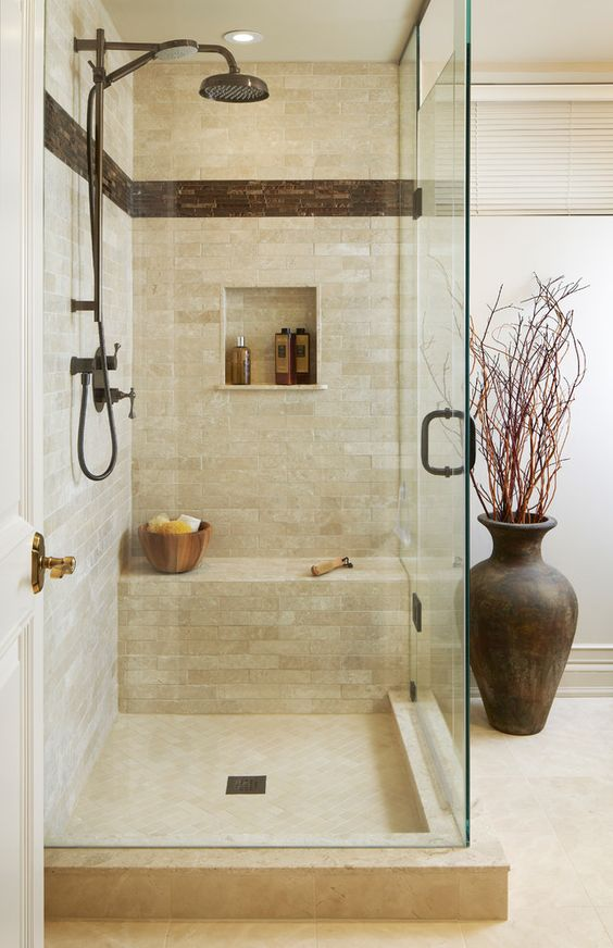 a small and welcoming earthy shower space with a built-in bench, dark hardware and tiles for a touch of drama