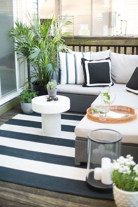 a small black and white deck with an L-shaped upholstered bench, a coffee table, a candle lantern and potted greenery