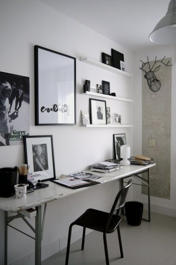 a small black and white home office with a shabby chic desk, a black chair, artworks and shelves