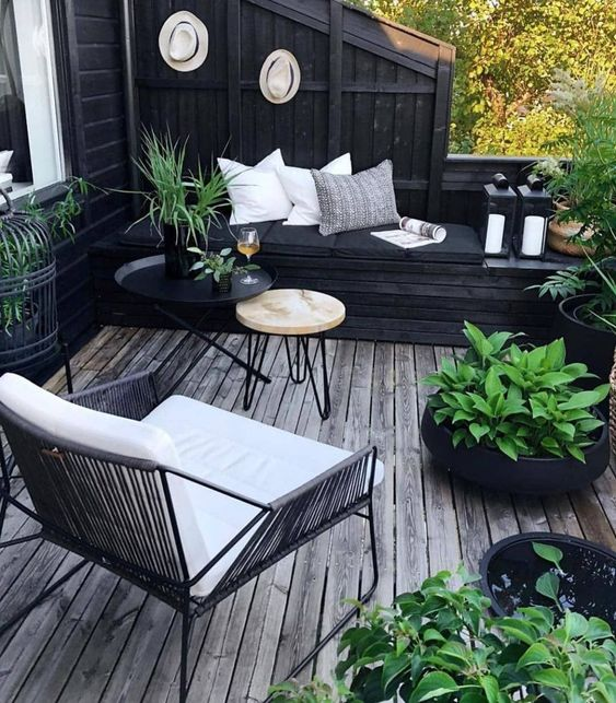 a small boho inspired black and white deck with modern furniture, pillows, potted greenery to refresh the space