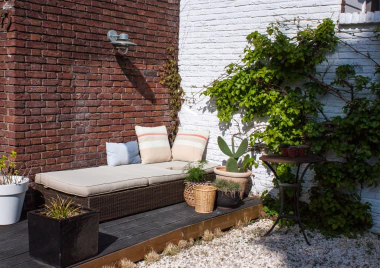 a small dark deck with an upholstered bench, potted greenery, cacti and succulents, a wall lamp and a side table