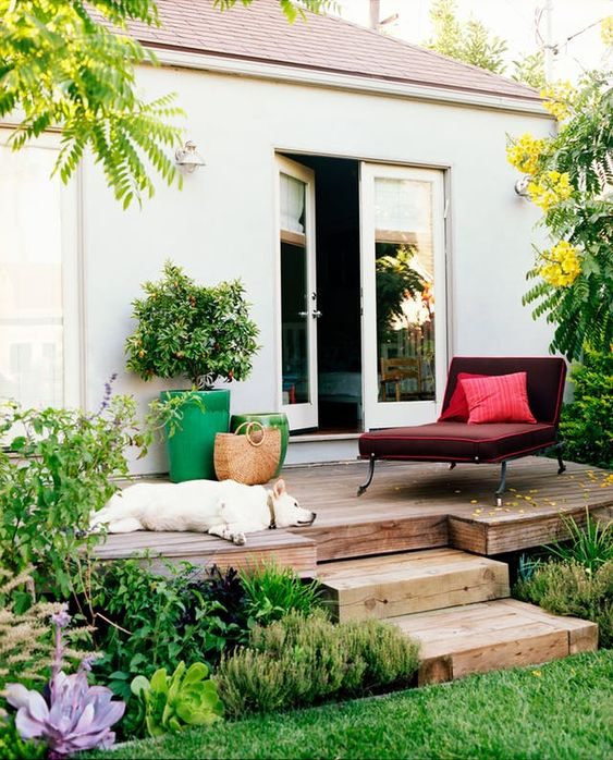 a small deck with a comfortable burgundy lounger, a couple of bright planters and a relaxed pup