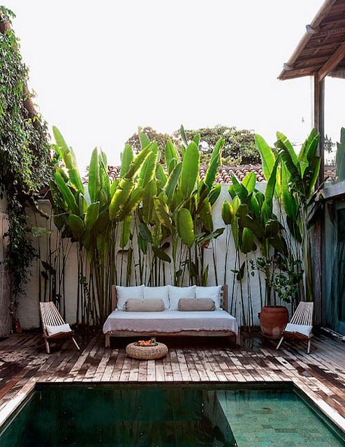 a small deck with a comfortable daybed, some folding chairs, a jute ottoman and greenery