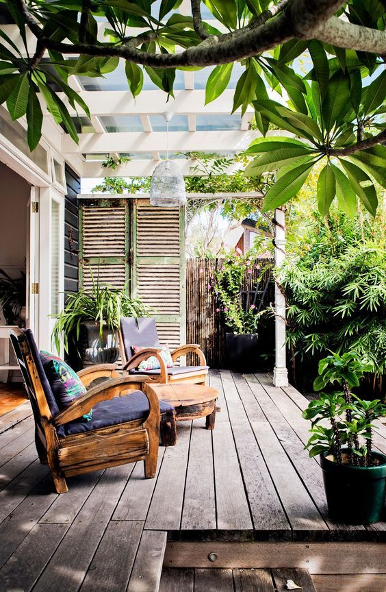 a small deck with a couple of whimsy wooden chairs, a side table and some potted greenery for a welcoming feel