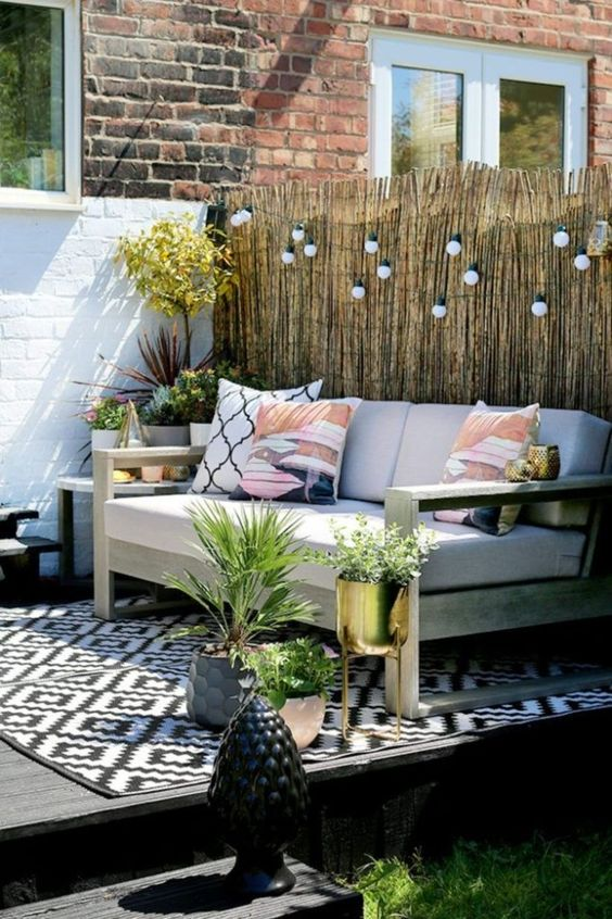 a small deck with a large comfortable sofa, lights over it and lots of potted greenery and blooms