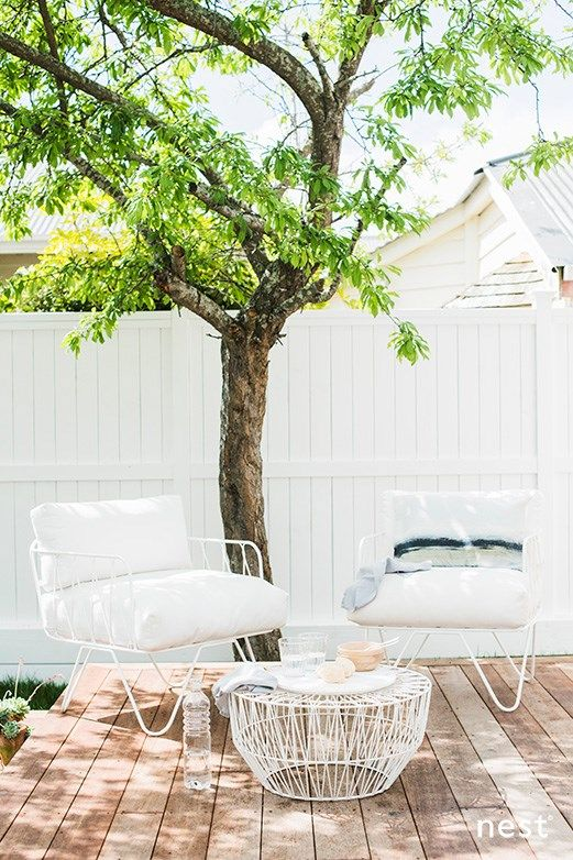 a small deck with a living tree, simple and stylish white furniture and a coffee table to serve meals