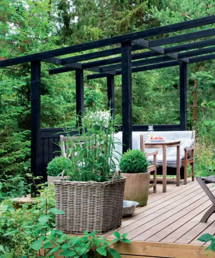 a small deck with a roof over it to hang curtains, a comfortable dining space with simpel wooden furniture and potted greenery
