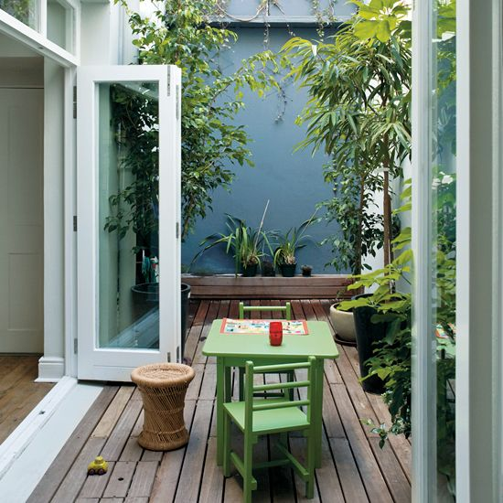 a small deck with green furniture, potted greenery and a rattan side table feels very welcoming and secluded