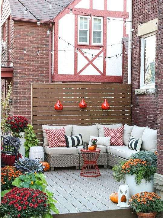 a small fall-inspired deck with an L-shaped upholstered bench, colorful pillows and potted blooms