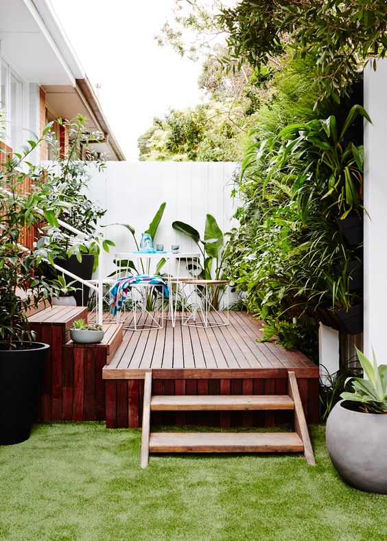 a small rich stained wooden deck with simple metal and plywood furniture and lots of greenery around for freshness