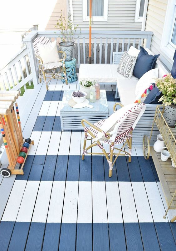 a small striped deck with rattan furniture, an L-shaped bench with pillows, potted greenery and a blue coffee table