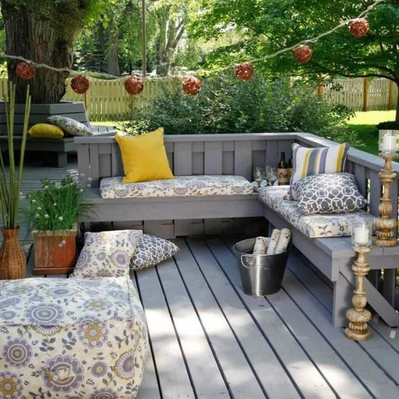 a small weathered deck with a built-in L-shaped bench, printed cushions and pillows, some potted greenery