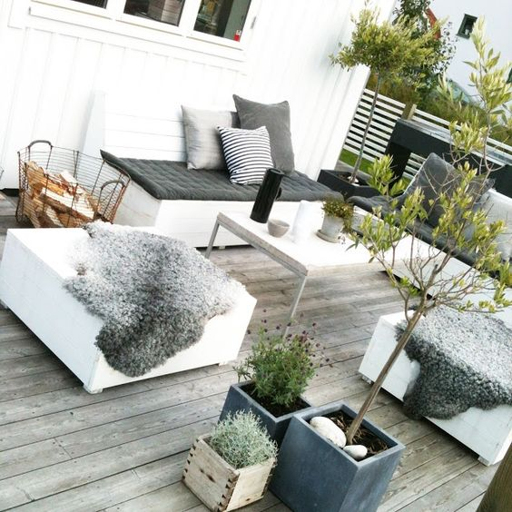 a small weathered wood deck with contemporary furniture, potted greenery and blooms and screen for privacy