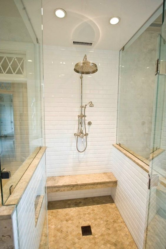 a smll shower space with white tiles, a floating earthy bench and a matching floor plus glass walls on two sides
