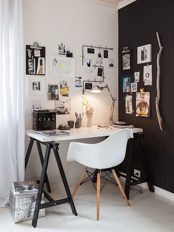 a stylish Scandinavian home office with a black and white wall, a trestle black and white desk and some artworks in black and white