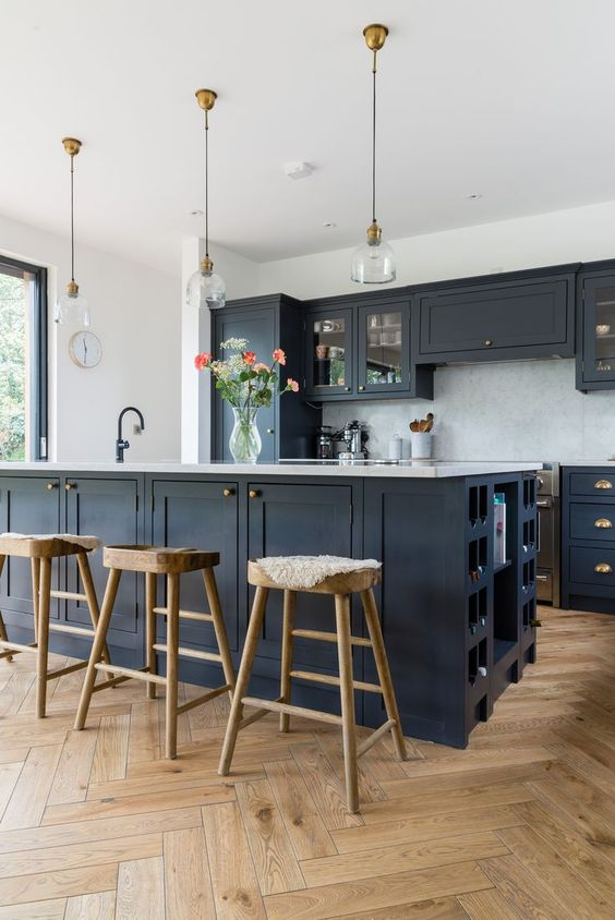 a stylish black farmhouse kitchen with white countertops and touches of wood to soften the look