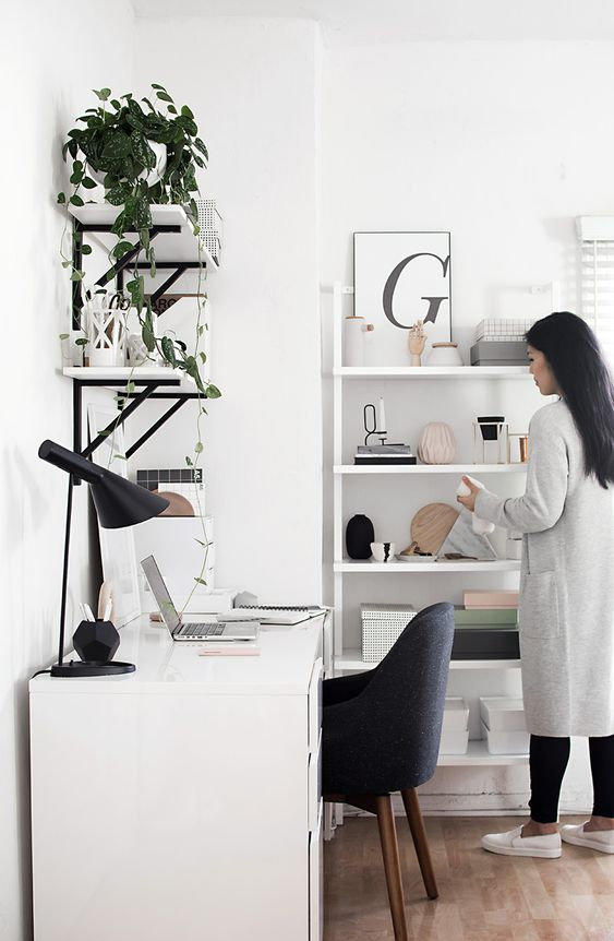 a stylish contemporary home office in white, with a black chair, lamp, black and white shelves on the wall