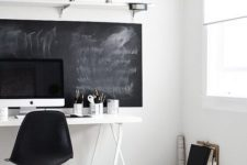 a stylish eclectic home office with a chalkboard, a white desk, a black chair and some white boxes for storage