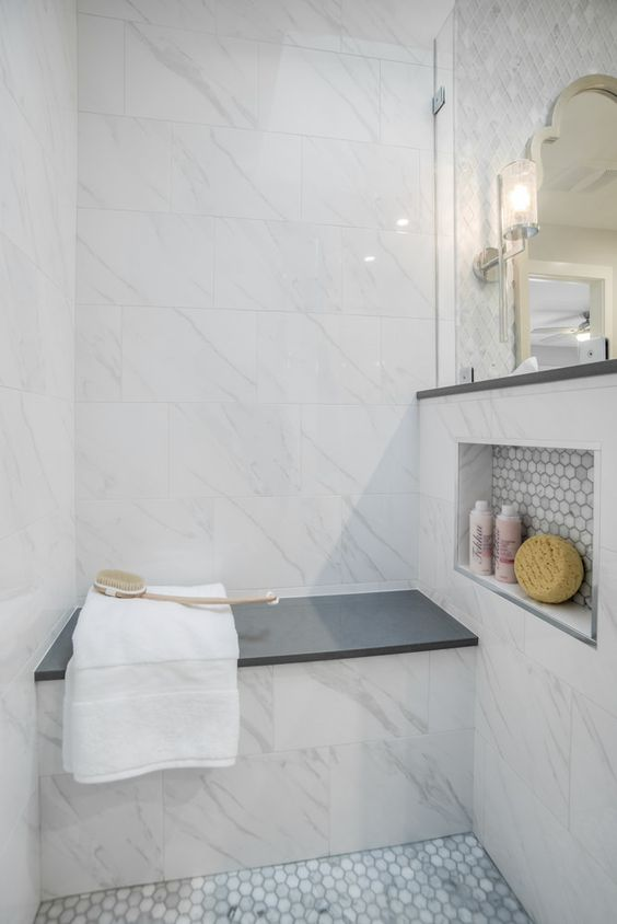 a stylish small shower space done with marble tiles, marble penny tiles, a built-in bench with a black seat