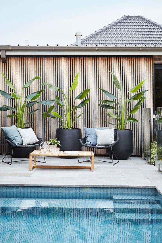 a tiled pool deck with a wooden table, some rattan chairs with pillows and potted greenery in black planters
