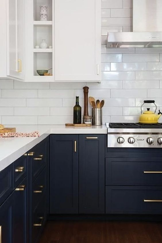 a trendy two tone kitchen with white and black cabinets, white countertops and gold hardware plus a white subway tile backsplash
