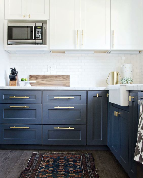 a trendy two tone navy and white kitchen with white countertops and gold hardware that give it a more modern feel