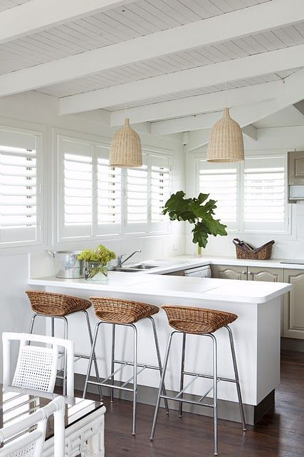 a tropial kitchen in grey and white, with wicker lampshades, wicker stools, grey cabinets and tropical plants