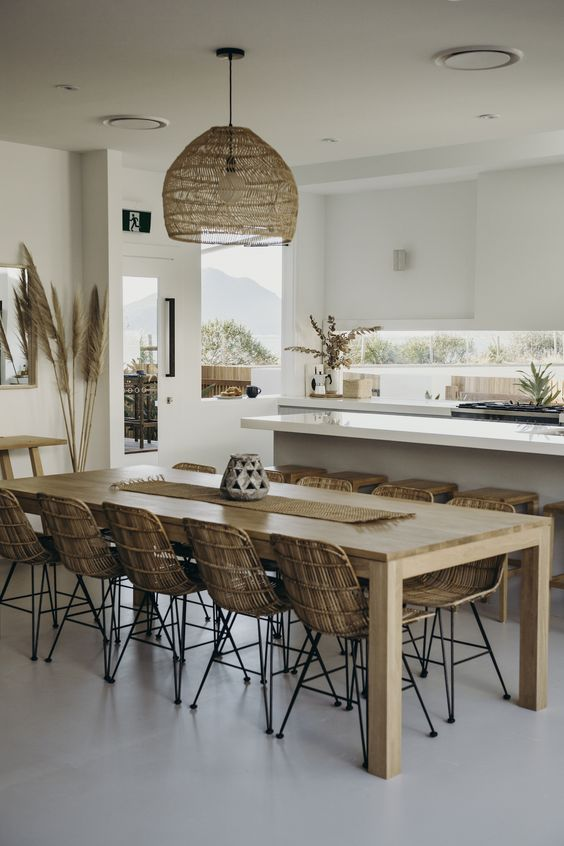 a tropical kitchen with sleek white cabinets, a wicker lampshade, rattan chairs, tropical plants and pampas grass