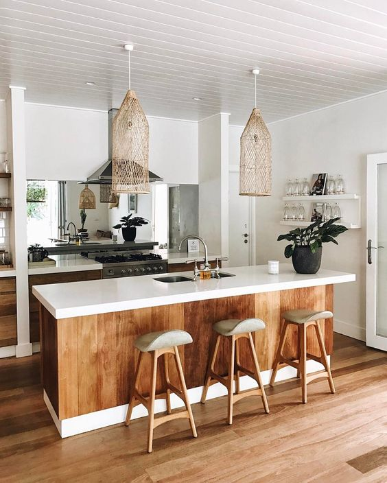 a tropical kitchen with white cabinets, stained wood covering the kitchen island, wooden stools, wicker lamps and a mirror backsplash