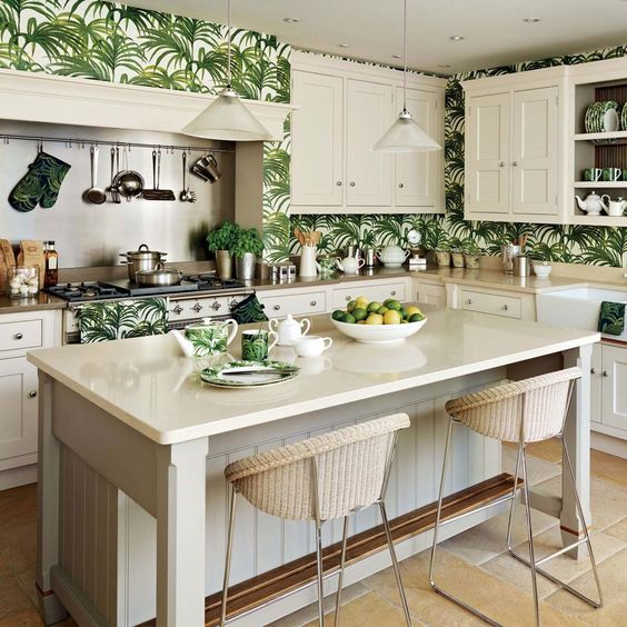 a vintage-inspired tropical kitchen with creamy cabinets and tropical leaf wallpaper wall over plus wicker stools
