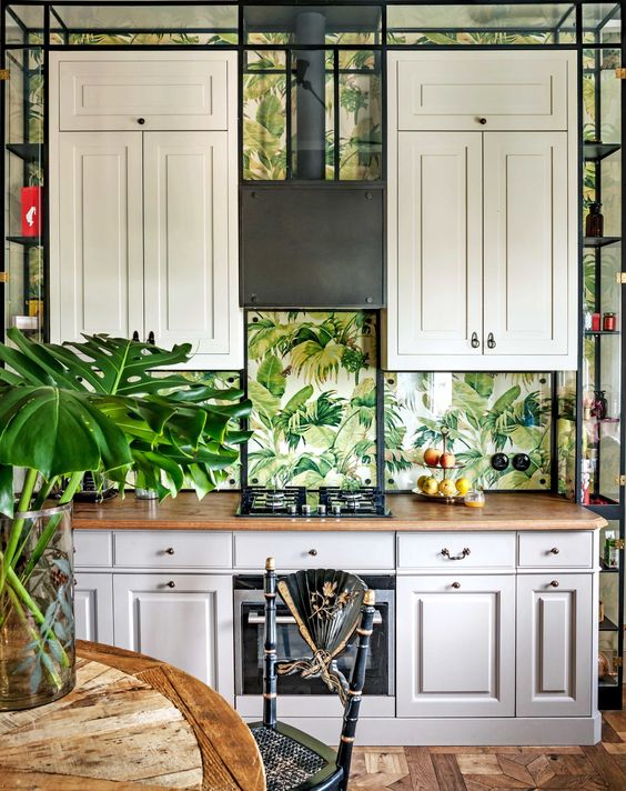 a vintage tropical kitchen with creamy cabinets, a wooden table, black rattan chairs and tropical leaf wallpaper