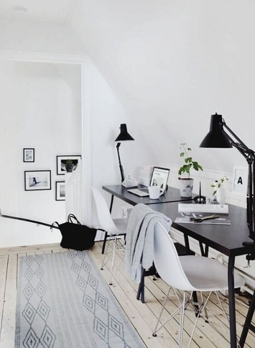 a welcoming Scandinavian space with a black desk and white chairs, black lamps and printed rugs