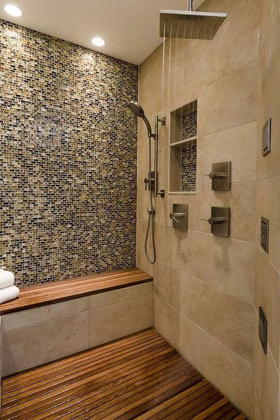 a welcoming earthy shower with various types of tiles that match, a teak floor and a built-in bench with a teak seat