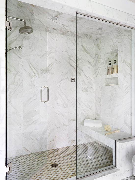 a white marble shower with a floating bench and a mosaic floor is a stylish and refined idea
