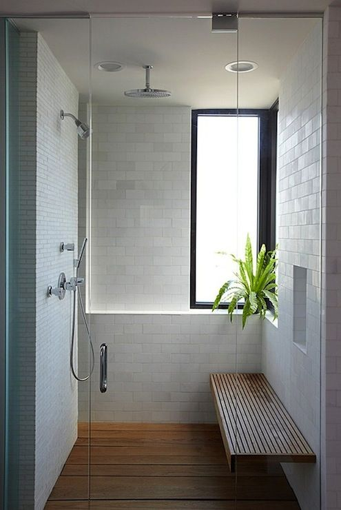 a white shower space with a frosted glass window, a floating wooden bench and a matching floor plus a potted plant