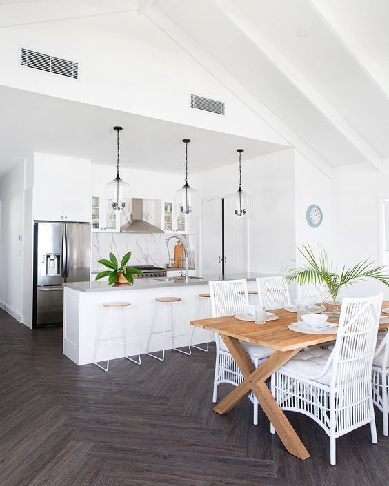 a white tropical kitchen with a marble backsplash, glass pendant lamps, wood and metal stools and a dining space with a wooden table and white rattan chairs
